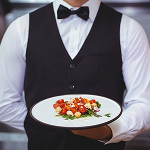 Server in a uniform holding a plate of food