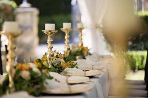 long table with flowers, linens and plates outdoors