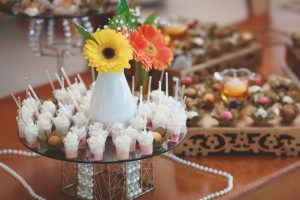 wooden table with mini appetizers and flowers displayed